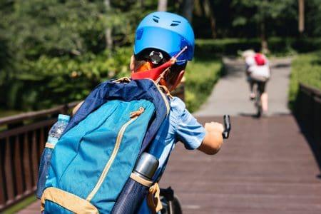 copil merge pe bicicletă cu echipament sportiv