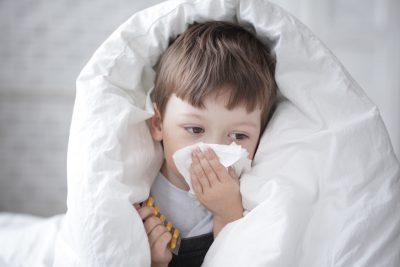 copil răcit învelit cu plapuma își suflă nasul și e trist