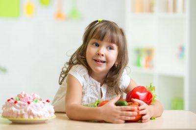 copil care alege fructe și legume, deci mâncare sănătoasă, în locul dulciurilor
