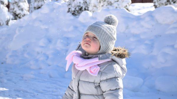 copil fericit se joacă iarna în parc