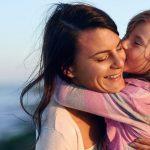 iubirea dintre mama si copil. fetita isi strange in brate si saruta mama