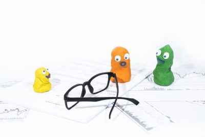 Funny figures made from Play Clay on white documents with glasses. Abstract of business document routine.