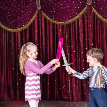 Young Clowns Having Sword Fight on Stage with Props, Girl Holding Large Pink Comb While Boy Holds Toy Sword