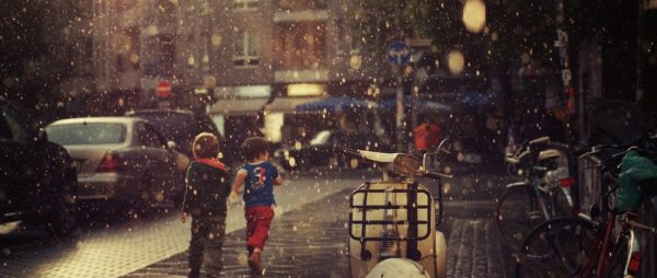 Two kids in rain in the city