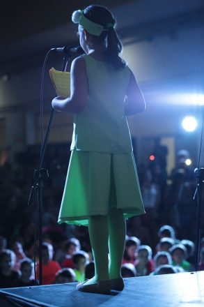 girl on stage performing a reading