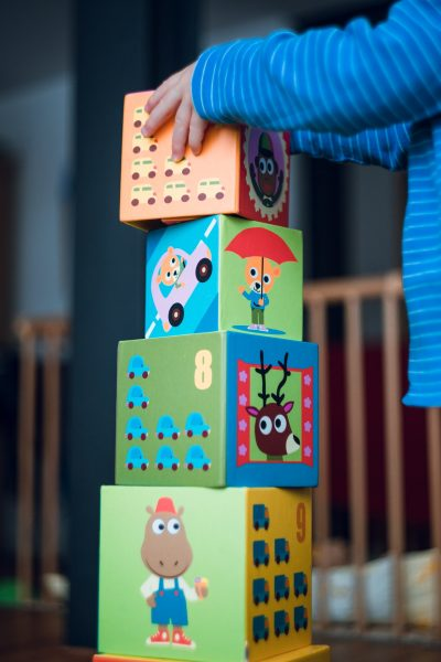 Toddler piling cubes wth drawings