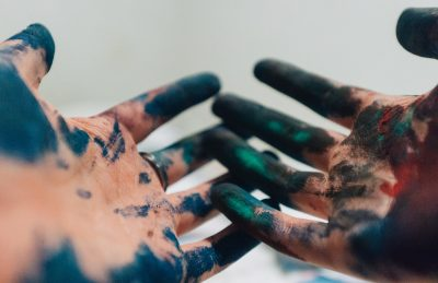 hands splashed with dark paint